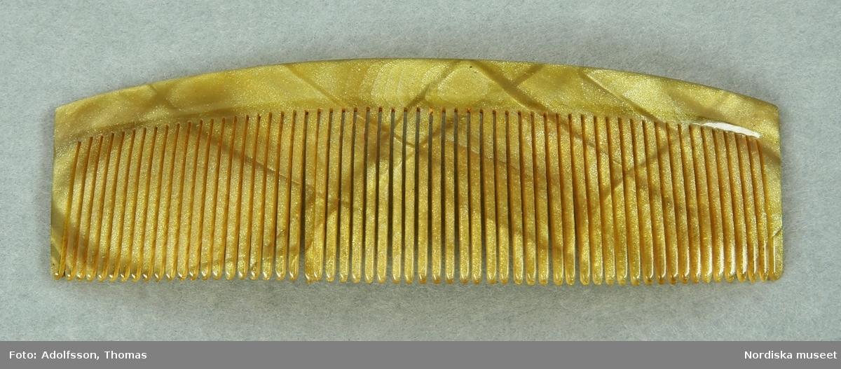 Materialet är cellulosanitrat enligt konservator Thea Winther 2010.