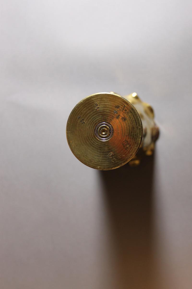 En tomhylse etter ammunisjon til uidentifisert våpen har blitt bearbeidet til en vase. Metallet er messingfarget, med noen slitte flekker, særlig på innsiden av åpningen. Mulig rust. Kanten er bølgete, trolig banket ut, og skråner utover i toppen. På noen av utoverbølgene har det gått av små biter, eller har blitt sprekker. Dette kan ha skjedd da den ble bearbeidet.  Mønster og tekst er banket inn med et punktredskap, slik at alt er satt sammen av prikker.  inni vasen stikker det opp en hul spiss i midten, som er fra ammunisjonsfunksjonen.