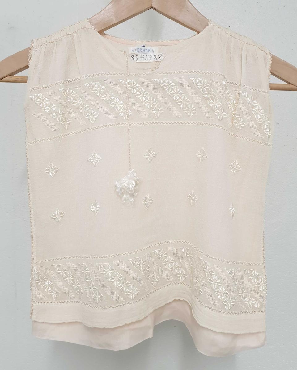 Gammelrosa bluse uten ermer for pike. Blusen har silkefôr, og transparent overflate med broderier og hullsøm.