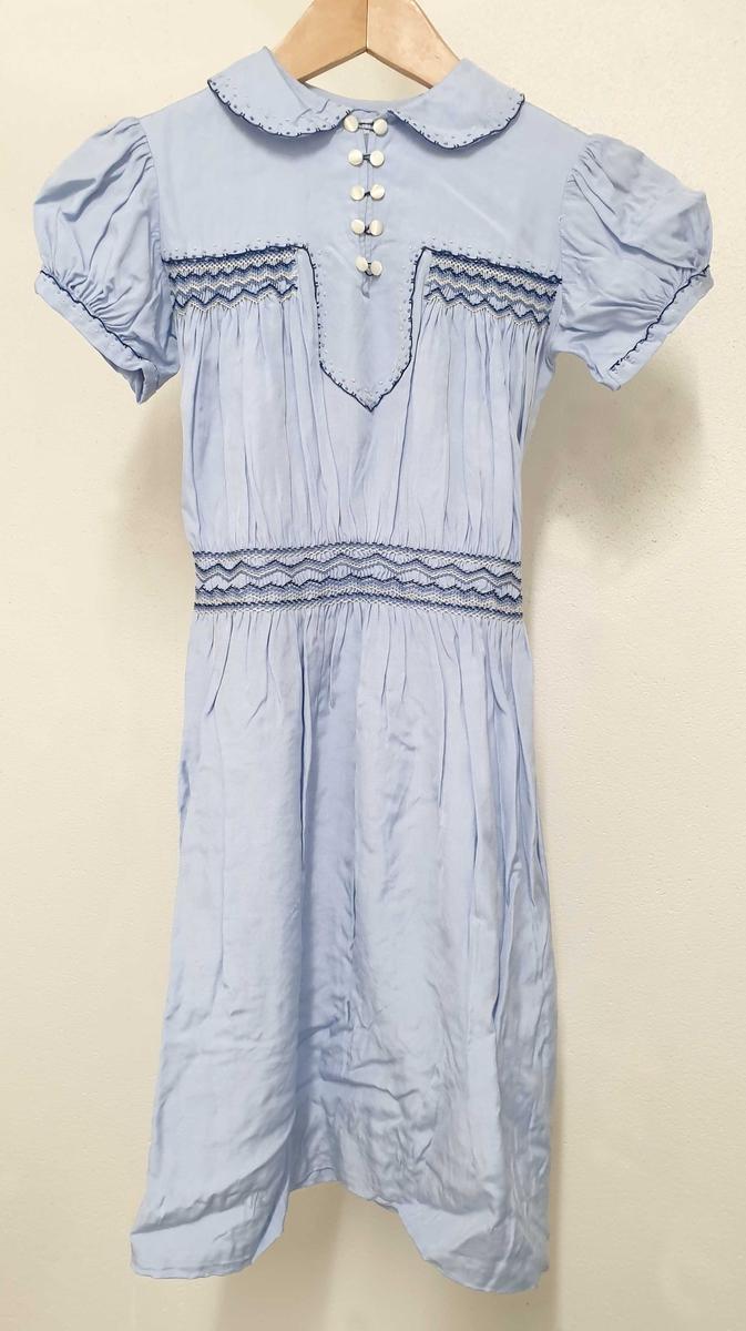 Blå sommerkjole av bomull for pike, med knapper og brodering, og med sløyfe påryggen.