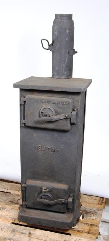 """Kamin (Jvm 19278:1) av järn med en lucka upptill där man kan stoppa in vedträn, överkanten av luckan är märkt """"HUSQVARNA 65A J"""". Luckan öppnas och stängs med ett handtag som man vrider uppåt för att öppna och ner till vågrätt läge vid stängning. På mitten av kaminen är det märkt """"SJ Mob"""". Nederkanten av kaminen har en lucka som fungerar som den ovan, man öppnar luckan för att ta ut den behållare där all aska har samlats. Luckans överkant har ett litet rektangulärt hål där handtaget för spjället sticker ut. Spjället drar man i för att släppa ner aska i behållaren innan man plockar ur den. Båda luckorna har en ventil i mitten som man kan skruva ut för att reglera värme och syre till elden. Nedre delen av skorstenen är fäst vid kaminen och i den finns det en lucka med ett handtag på utsidan, där man kan reglera hur mycket rök som ska släppas ut. Luckan regleras så att när man öppnar ventilerna så ska det inte komma ut rök, utan all rök ska ledas uppåt. När sedan elden har slocknat kan man stänga luckan för att förhindra att värme läcker ut i skorstenen istället för i rummet.  Skorstenen (Jvm 19278:2) Längd: 240 mm Bredd: 200 mm Höjd: 1140 mm Diameter: 105 mm Skorstenen består av mindre rördelar som är sammansvetsade. Skorstenen är lätt böjd i nederdelen och mera  böjd i överdelen. På slutet av skorstenen sitter ett litet tak en bit ovanför utsläppet som hindrar regn från att komma ner i röret.  Golvskydd (Jvm 19278:3) i plåt. Längd: 700 mm Bred: 700 mm Höjd: 100 mm. Golvskyddet är till för att skydda golvet där kaminen står, man ställer kaminen på plåten och skruvar fast den genom plåten i golvet. Plåten har färdiga hål för att passa till kaminen och även till att passa en rund kamin."""