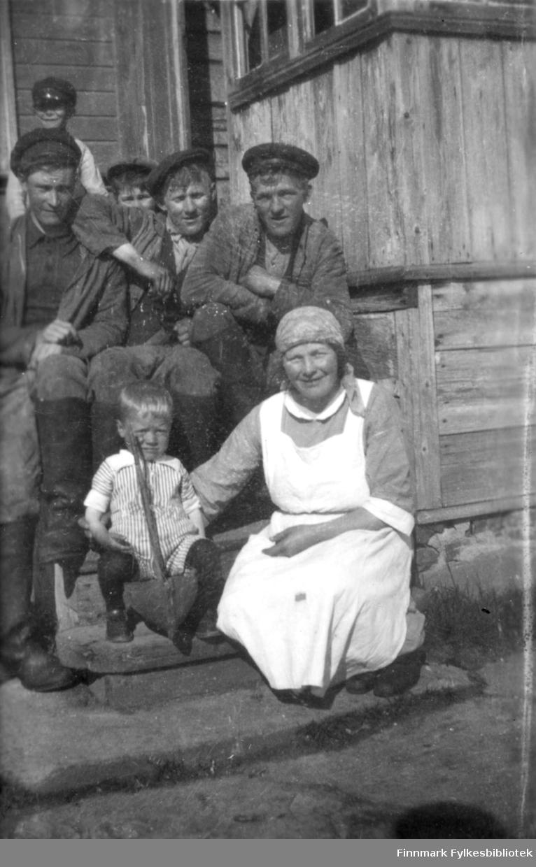 En dame, tre menn og tre barn sitter på trappa. Stedet er Salttjern.