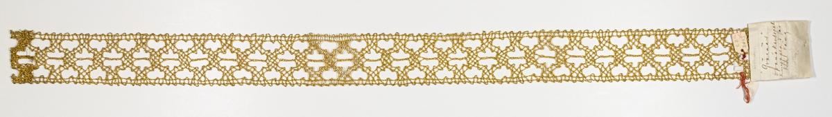 """Mellanspets, 79 x 5. """"Qvarmans"""". Guldtråd. Från Qvarmansgården i Ovanåker. Hälsingland, Ovanåker. Äldre katalogisering av Elisabeth Thorman (enl. uppgift).  Längd: 77 cm          Bredd: 5,2 cm Spunnet guld (möjligen förgyllning) om kärna av gult troligen bomullsgarn. Knypplingen utförd med dubbelslag och flätor. Mönstret bildar trekantiga håligheter längs spetsen. Spetsen är fållad i ena änden med gul tråd. Enligt Föreningen Svenska Spetsars arbetsritningar för Ovanåkersspetsar publ. 1974 heter mönstret """"Kvarman"""". Inger Danielsson sept. 1981."""