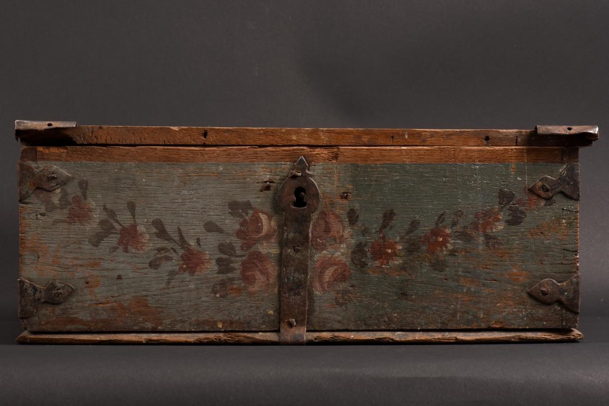 Rektangulärt, bemålat skrin med plant lock tillverkat av ek. Beslag, gångjärn och handtag är tillverkade av järn. Skrinet är målat i blått och runt om på sidorna och framsidan av skrinet finns en blad- och blomstergirland målad i rött, vitt och grönt. På lockets ovansida en liknande girland, men med mycket bortnött färg. Smidda handtag på sidorna. På insidan av locket finns rester av papper med otydbar skrift. Lockets list på framsidan saknas, och de två andra är sekundära.