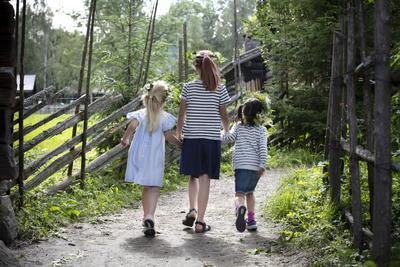 3 jenter med blomsterkranser går hånd i hånd. Foto/Photo