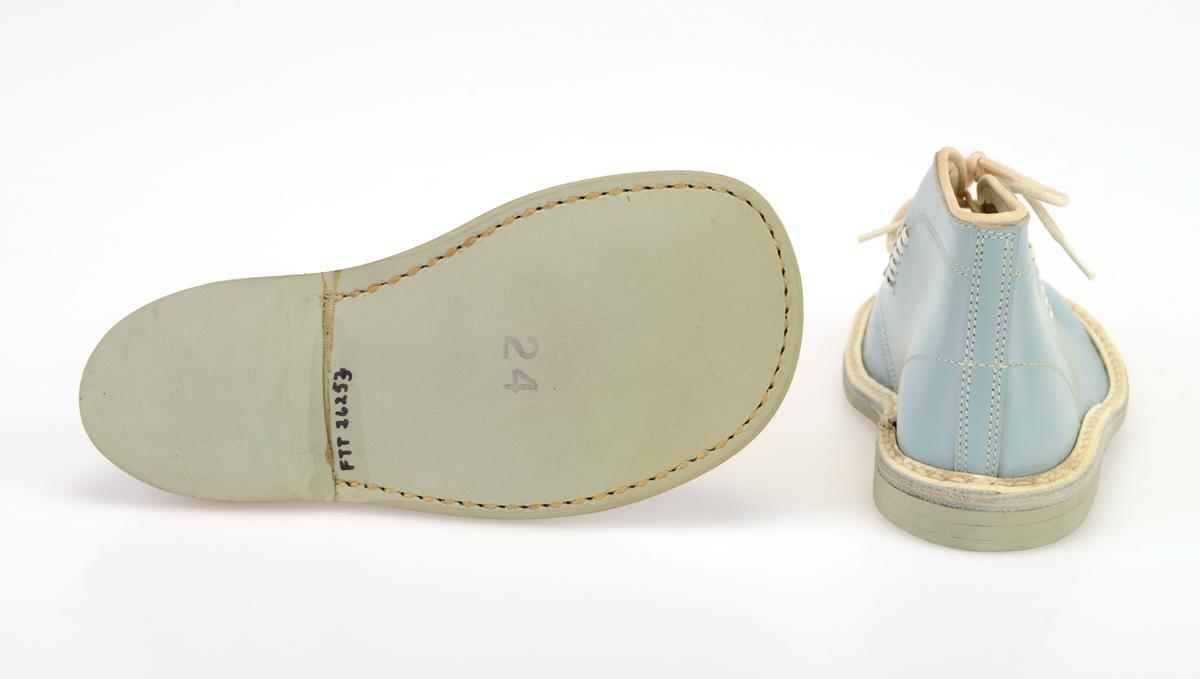 Et par barnesko i størrelse 24 i skoeske med silkepapir. Skoene er i lyst blått skinn med lysegrå såle av kunstlær. De er randsydde. Kanten med randsøm er av hvitt kunstskinn. I front er det 3 par hull med maljer for snøring. Under snøringen er det en enkel tunge av lyst blått skinn. Skoene har hvite, runde skolisser. Det er sømdekor på skoene. Det er også seks hull på hver side med hvite kunstlærlisser tredd igjennom. Langs kanten innvendig er det en takkete kant. Skoene ligger i en skoeske av papp som er stiftet sammen. På den ene kortsiden er det trykt på fabrikkens navn, varemerke og logo samt artikkelnummer og størrelse. Logoen er en sirkel med en Nord-pil igjennom. Skoene er ikke brukt.