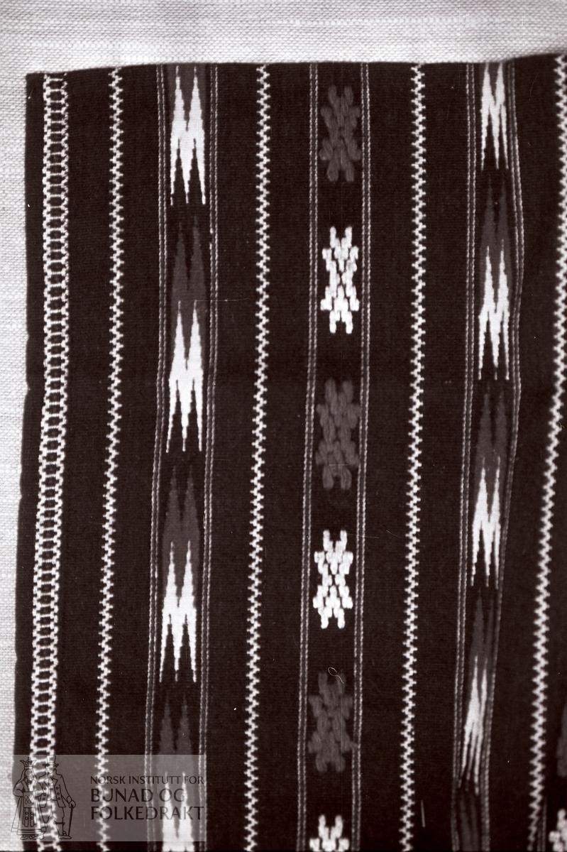 Nordhordlandsmessa 1974 - - - - - Nytt fra 1940. Vevd ull med lynildbord, åttebladroser og forskjellige border. Blå bunn, mønster i hvitt og rødt. Hvit bomullsrenning. Foldelagt med midtfold til linning av svart fôrsilke. Hekte i venstre side. Kastet over og sydd med maskin. Forklekanten også kastet med maskin. H.: 80,5 cm. Br.: 57 cm. Br. ved linning: 39 cm.
