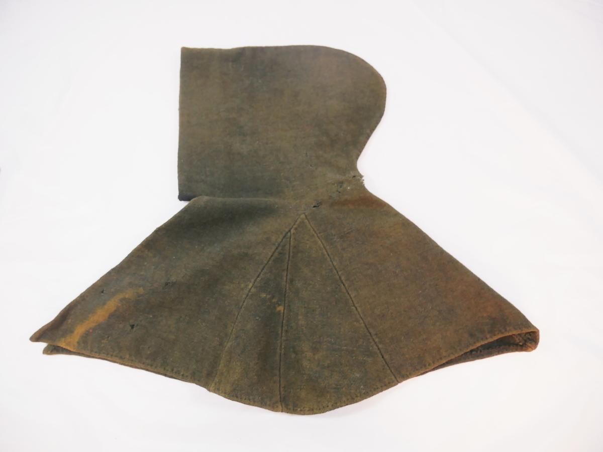 Hette med skulderslag, sydd av to stykke med kilar i begge sidene. Rundt hetta er skoning i raudt med trykk i svart. Skulderslaget har lukking over bringa med 3 sett krokar og hemper.
