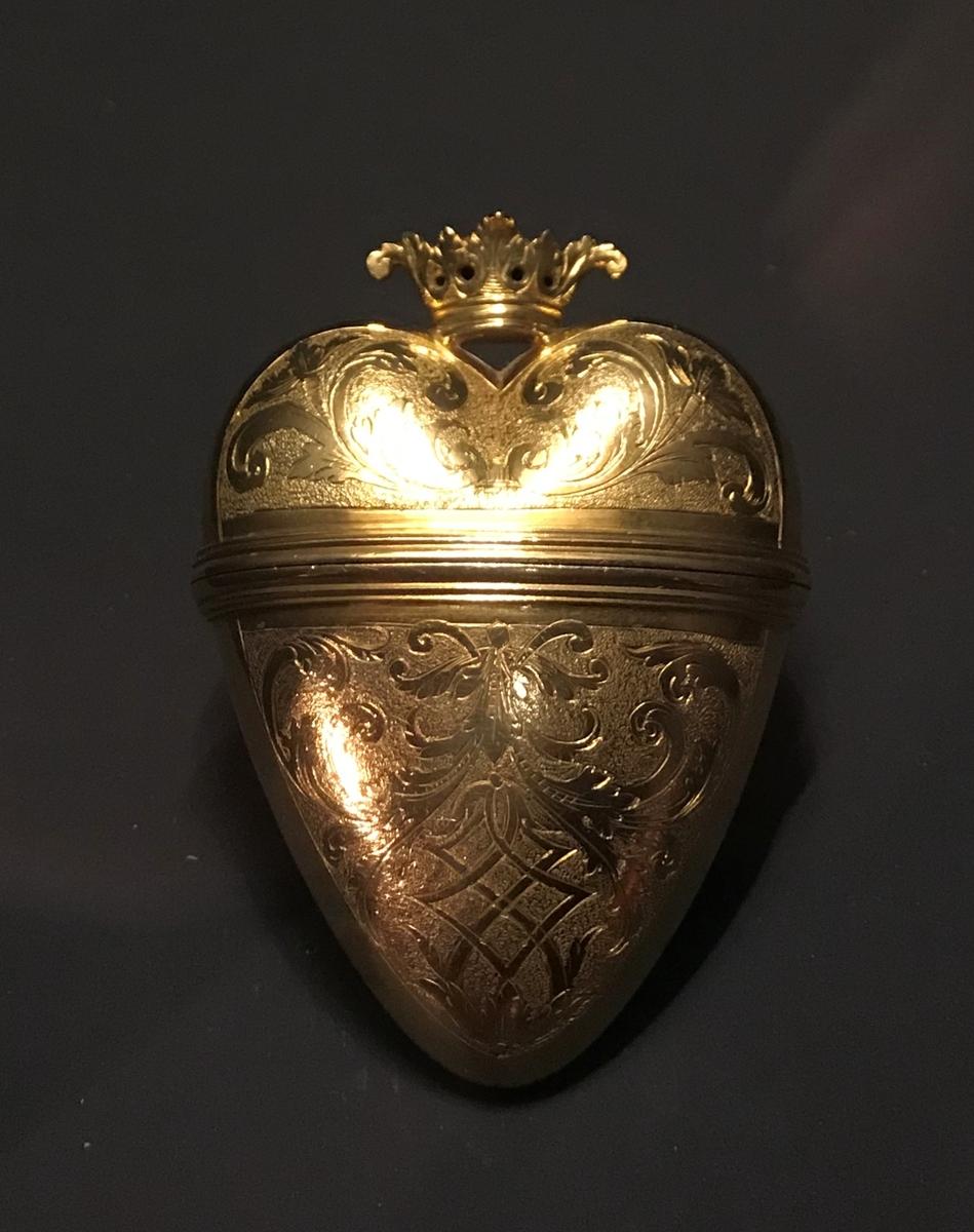 Luktevannshus i gull. Hjerteformet, hvor øvre del utgjør et hengslet lokk med kroneformet lokknapp. Begge sider har graverte forsiringer, i form av løv- og bladverk på punslet bunn.