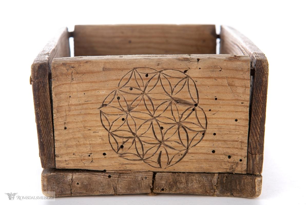 Eskens langsider har seksbladsroser i sirkel på en side, og sammenkomponerte, symmetriske figurer på den andre. På en kortside er det en sirkel med små, sammenkomponerte seksbladsroser. Kors under.