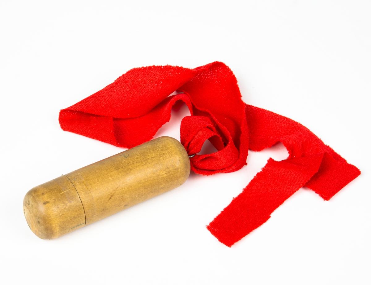 Rapporthylsa av trä. Rapporthylsan har ett 860 mm rött band. Inuti hylsan ligger en rullad papperslapp. På hylsan står adressen som meddelandet är ämnat till.