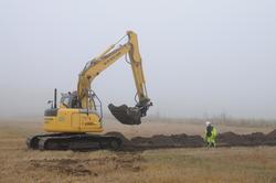 En grävmaskin gräver ett sökschakt övervakad av en arkeolog.