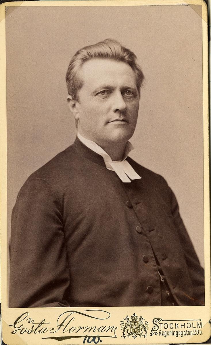 Foto av en man klädd i prästrock och prästkrage. Bröstbild, halvprofil. Ateljéfoto.