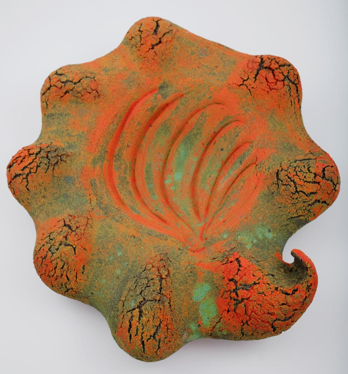 Stort, skulpturelt fat på rund fot. Skjell- eller planteform med bølgende omriss og en sammenknepet spiss. Tilnærmet rund fordypning i midten og skrånende, svulmende kanter. Formen er som et mykt, organisk landskap med kupler og daler - eller som tittelen tilsier, en plantevekst. I speilet er godset risset inn med seks bøyde streker; godset er ellers preget av sprekker og fordypninger. Overflaten er dekorert med glasurer i et flekkvist fargespill mellom oransje og grønt.