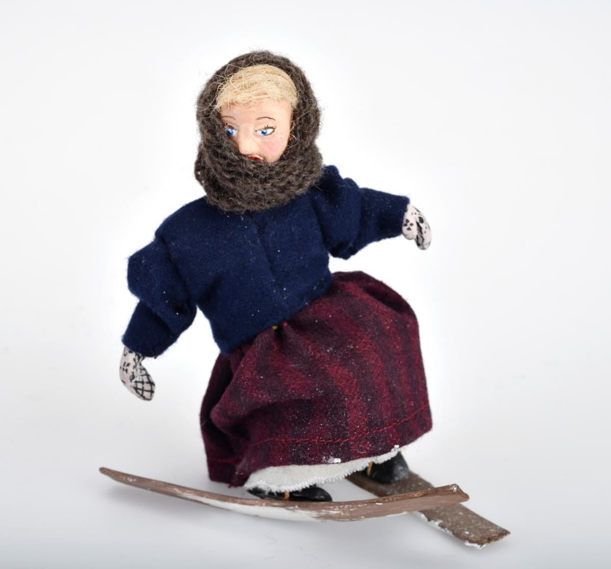Liten damefigur med ski på beina.