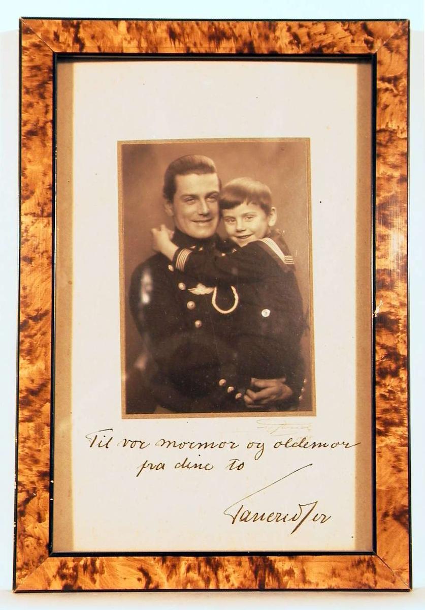 En voksen mann i uniform med en stor gutt i matrostøy på armen.