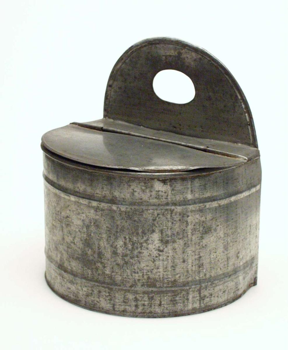 Kar til hvetemel laget i blikk. Det er halvsirkelformet med flatt bakstykke. Holderen har to riller og fast lokk.