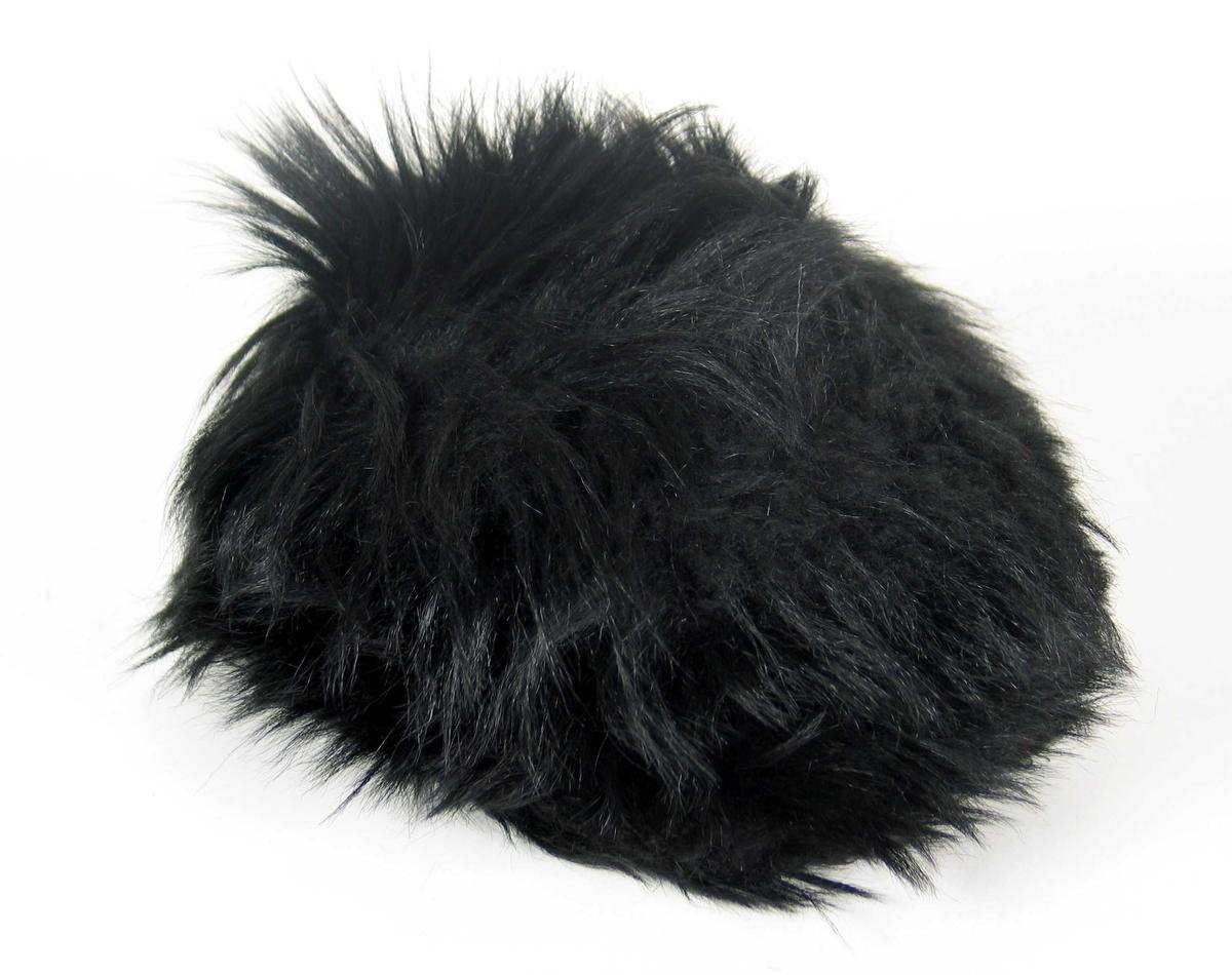 Lue i langhåret pels av ukjent type. Luen har et rundt issestykke og påsydd kant, 15 cm høy for luehøyden. Den har vattert, svart fôrsateng med rundt issestykke og kant, delt i to med to sømmer.