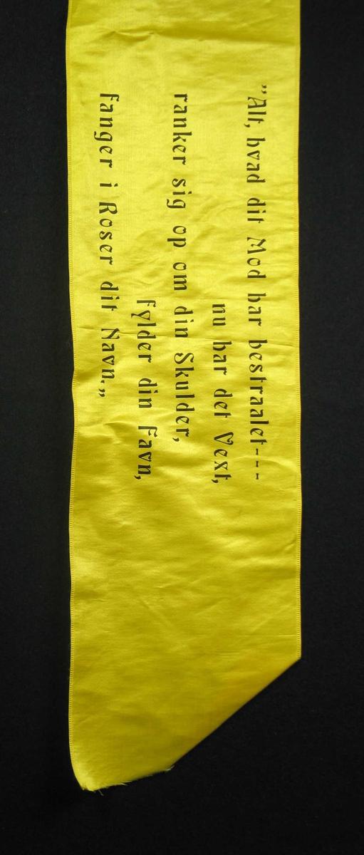 Begravelsessløyfe i gul silke med svart tekst.
