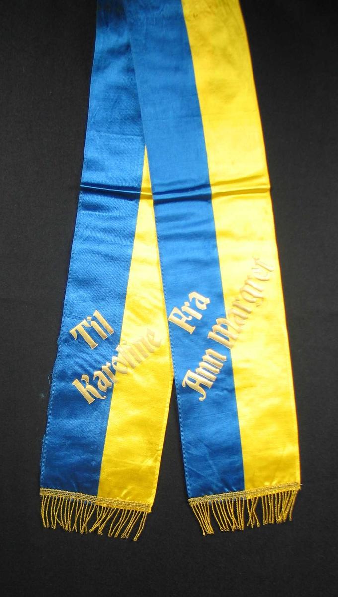 Begravelsessløyfe i gul og blå silke med tekst og frynser i gull.