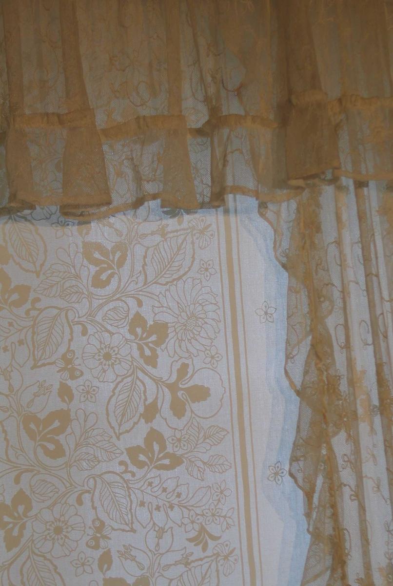 Hvit tyllgardin med maskinbroderi. Sidegardiner fald i sidene mot veggen og kappe 10 cm bred med smalt rynkehode mot vinduet og nederst med avrundet hjørne. Kappen har 10 cm bred rynkekappe med smalt rynkehode nederst. Motiv: Vertikalt løpende s-sving med to fylte blomster som vendes annenhver gang. En rapport: h 36, br 7. Hele gardinfaget er montert på gardinbrett med folder holdt på plass med knappenåler.