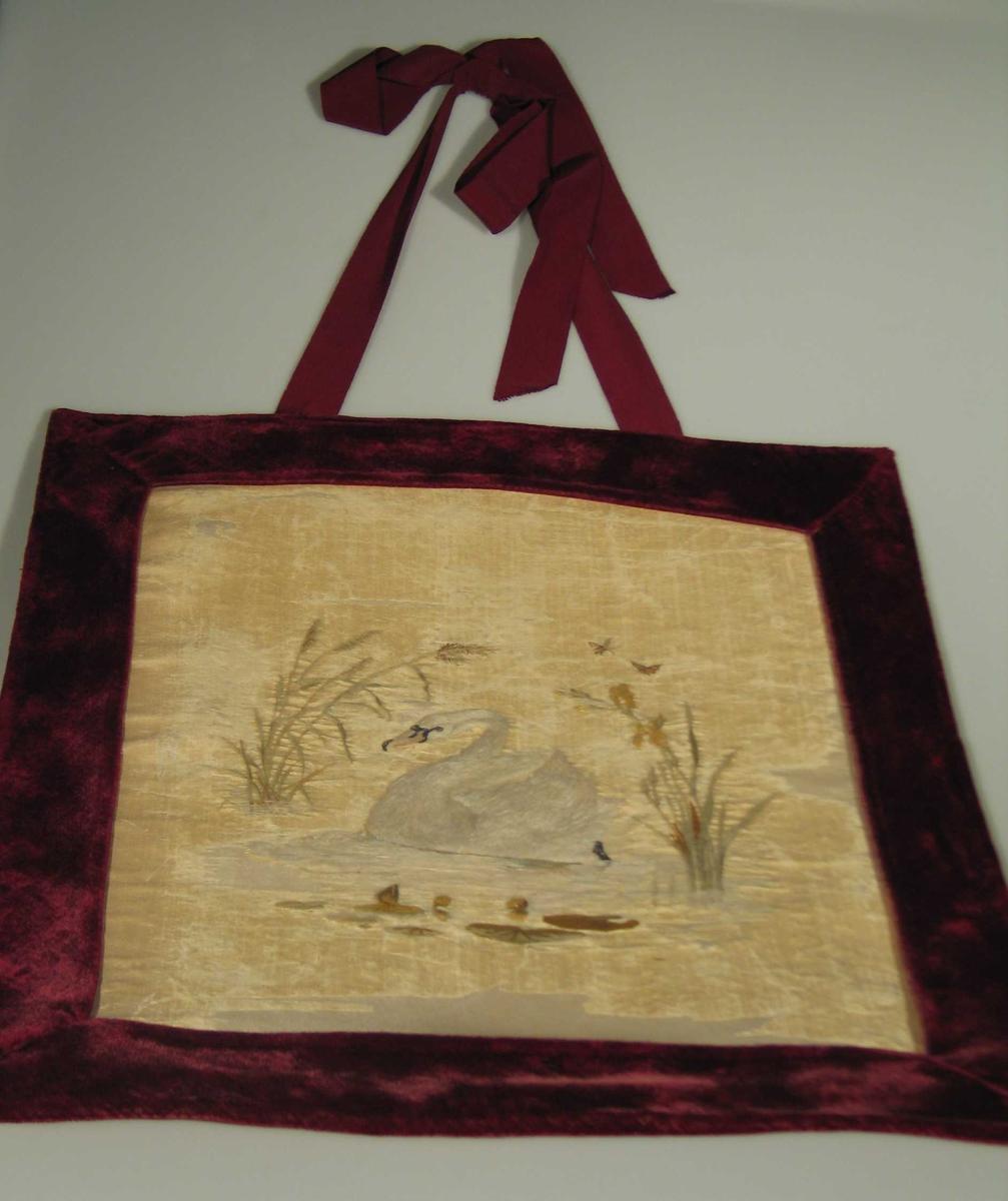 Rektangulært tekstilbilde med svanemotiv i krympet landskap. Fargene er beingul, hvit, mosegrønn, burgunderrød og svart. Bildet er av silke montert på papp med en rød fløyelsramme rundt. Det er benyttet forskjellige stingtyper. Henger i bånd.