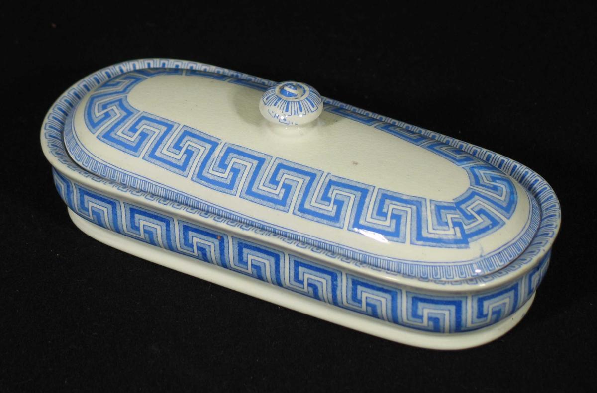 Hvit eske med lokk til tannbørster. Den er laget i steintøy dekorert med blå border. To riller innvendig