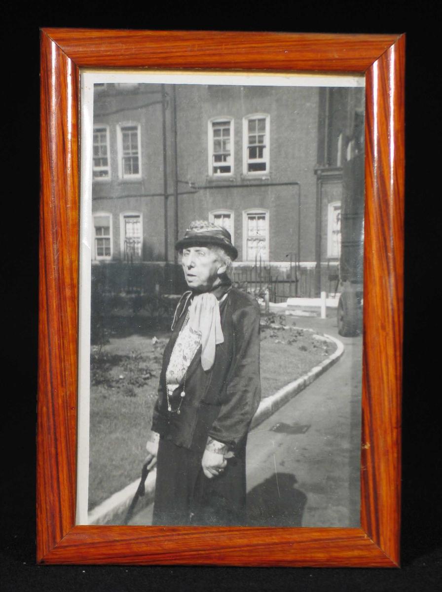 Eldre dame foran husfasade. Hun bærer hatt, mønstret bluse og langt kjede.
