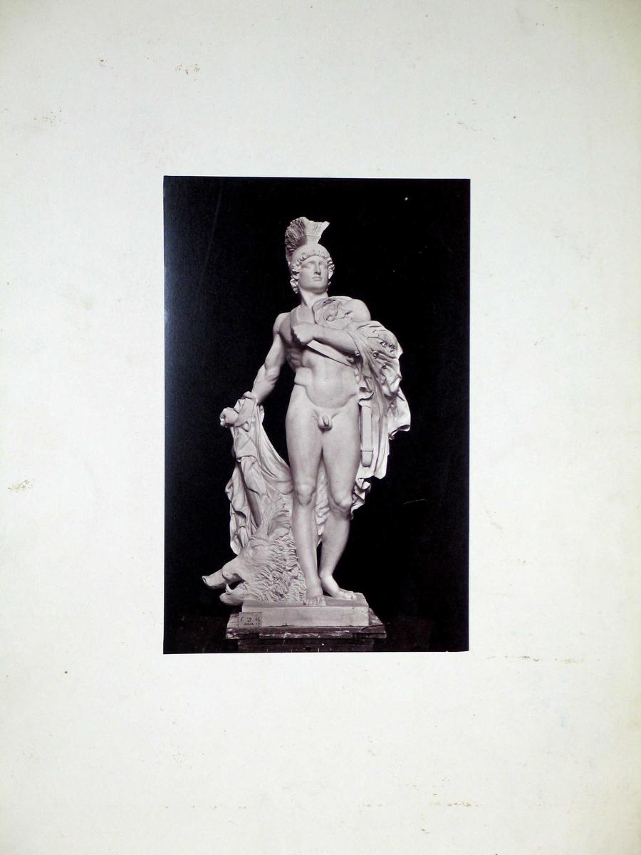 Fotografi av en skulptur limt på kartong.  Spikermerker øverst og nederst.