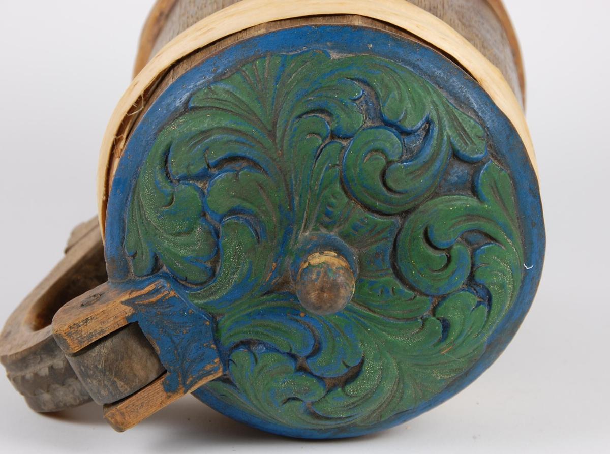 Kanne av furustaver. Lokket har dypt utskårete og grønnmalte akantusblader, blåmalt langs kanten. Lokkgrep kuleformet. Hanken er skåret ut av en stav, utskåret bård. Korpus har to gjorder oppe og nede (de øvre gjorder er av nyere dato).