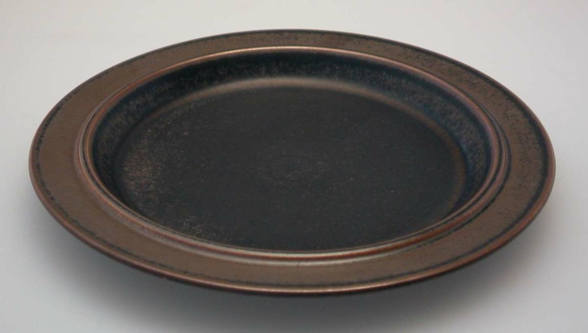 Åtte brune tallerkener i steingods.