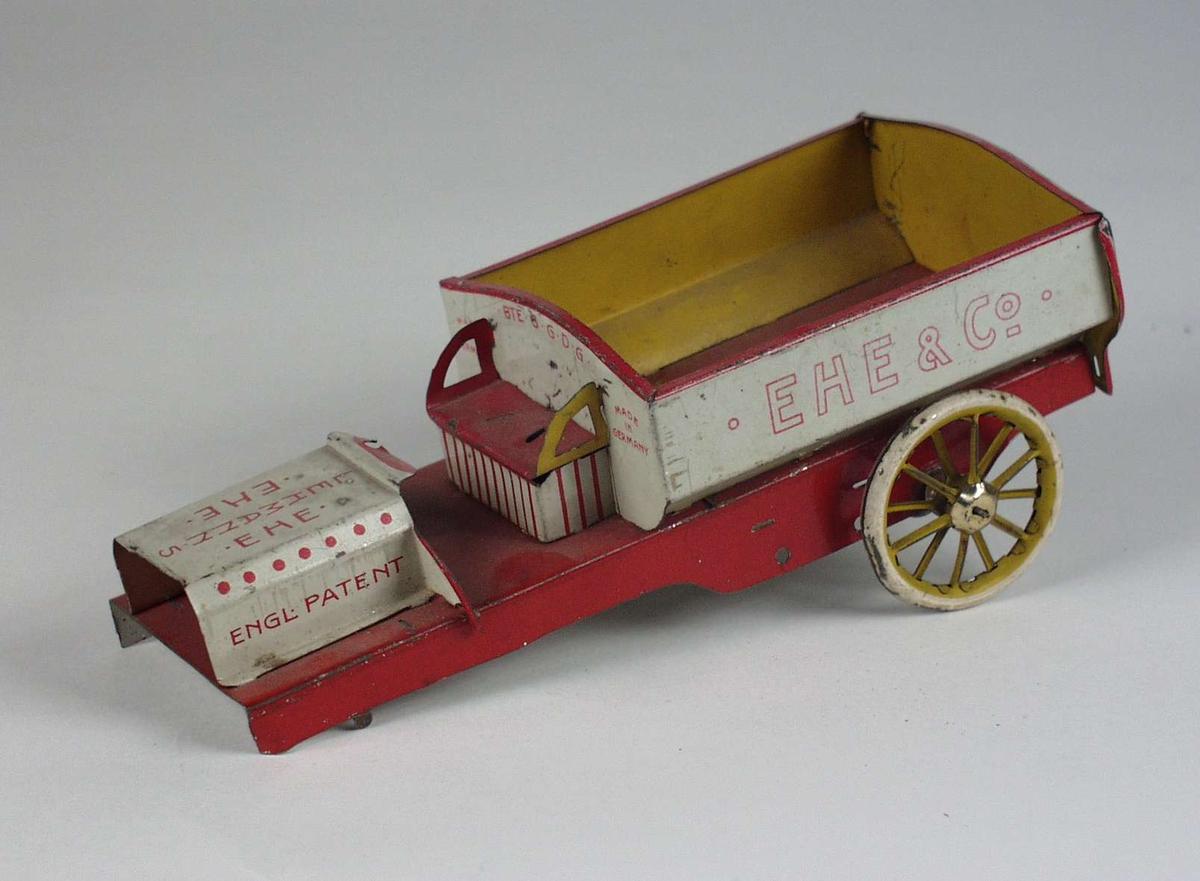 Rød og gul lekevogn laget i blikk.