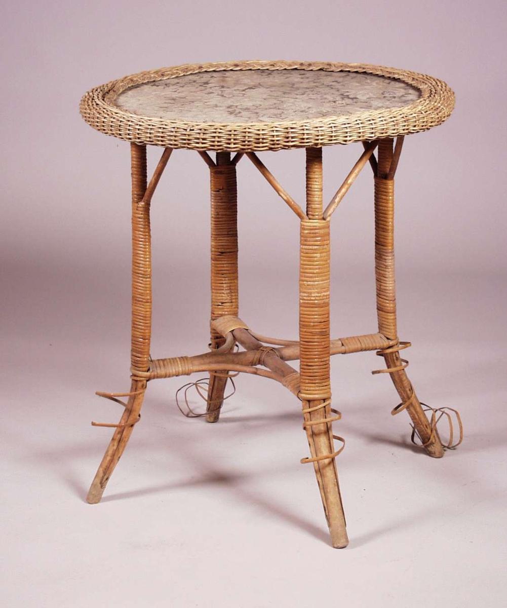 Kurvbord med en mønstret stoffplate. Under bordplaten er det kryssprosser som holder de fire benene sammen.