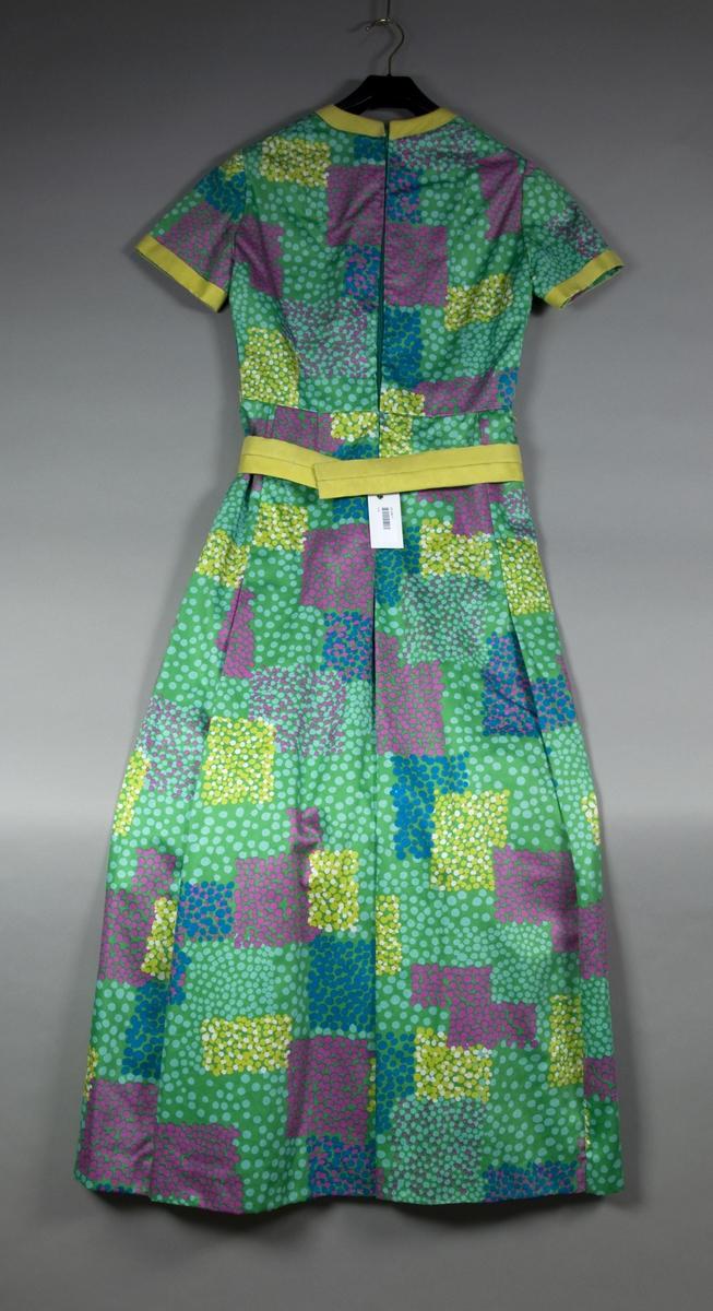 Lang kjole av mønstret bomull. Kjolen har korte ermer med oppslag av gult silkestoff, splitt i halsen forran med samme kanting som ermene. En hekte over glidelåslukningen i ryggen. Kjolen er avdelt i midjen og har skrådd skjørt med nedsydde folder. Kjolen har grønt silkefôr. Belte av gult silkestoff - jfr. kantinger.
