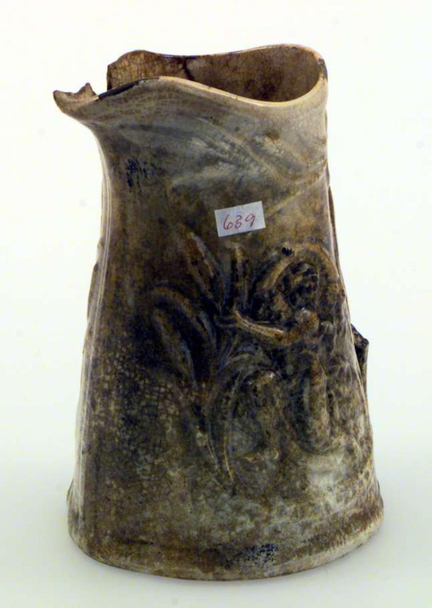Mugge i keramikk. Fargen er lys brun, 'melert'. Muggen er dekorert med to kvinnerelieffer. Hanken mangler. Det er et par sprekker i muggen og et bit er slått av ved nebbet.