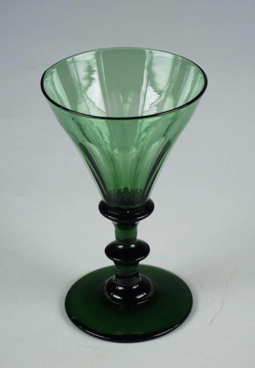 Olivengrønt vinglass med spiss, fasettslipt klokke og skive i stetten.