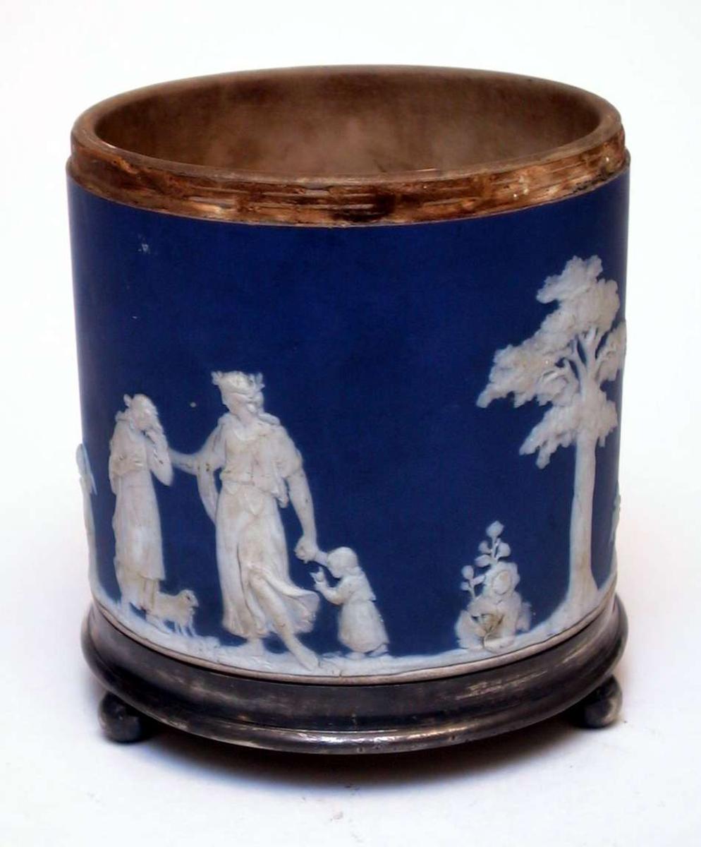 Wedgwoodkrukke i keramikk og sølv med rundt tverrsnitt og rette sider. Utsiden er blå og dekorert med hvite relieffer med klassiske motiver. Krukken har en fotring av sølv med tre føtter. Det mangler en ring langs overkanten av korpus. Krukken kan sannsynligvis ha hatt et lokk.