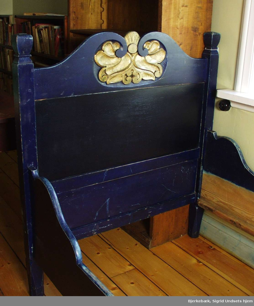 Blåmalt seng med utskåret bladverk på hodegjerde og fotende. Bladverket er forgylt.