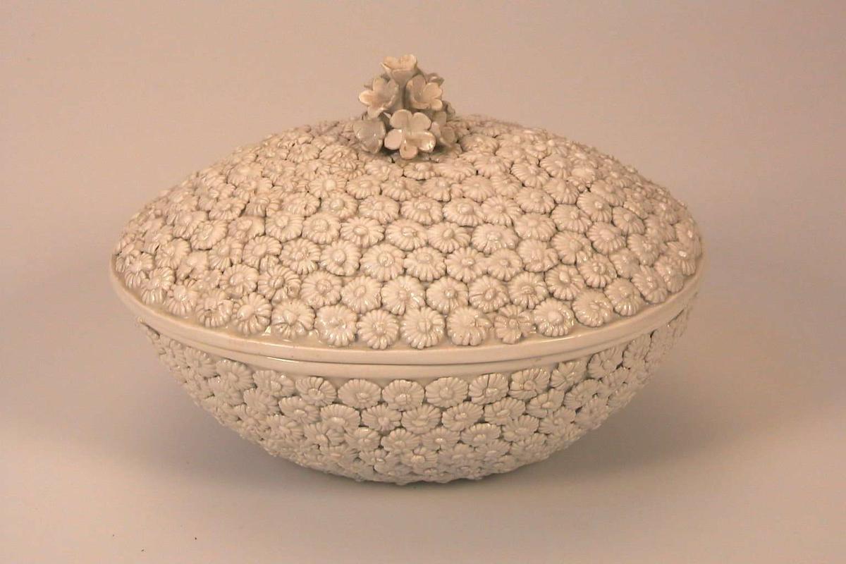 Bolle med lokk, glasert hvit og tett dekorert med påsatte, hvitglaserte blomster. Lokkgrepet er en bukett blomster.