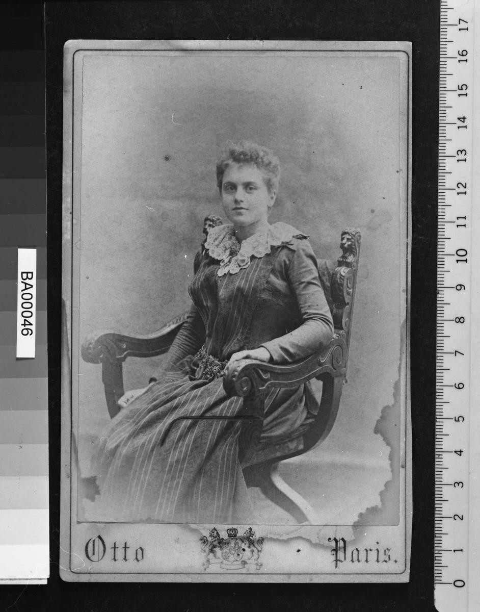 Portrett av en ung dame sittende i stor armstol i tre med utskjæringer. Hun bærer en mørk lang kjole med stripete forkle og en stor hvitt blondekrave. Om hoften hviler et tungt metallbelte. Den venstre arm hviler på armlenet, og hun ser direkte på betrakteren.