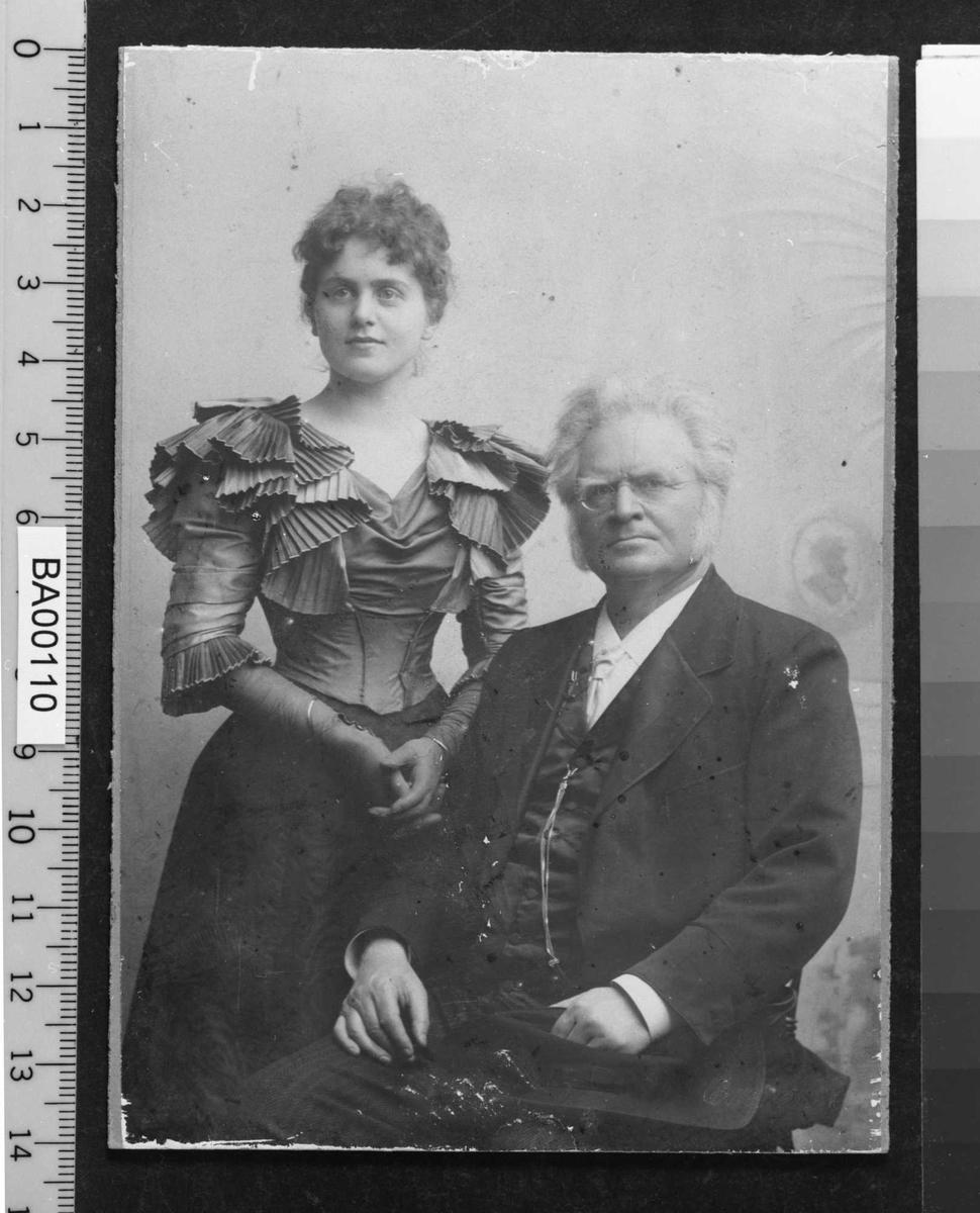 Atelierfotografi; dobbeltportrett, en ung dame stående i flott festkjole med hansker på, en eldre mann sittende på stol snudd 45¤ mot venstre inn foran henne. Han ser direkte på betrakteren.