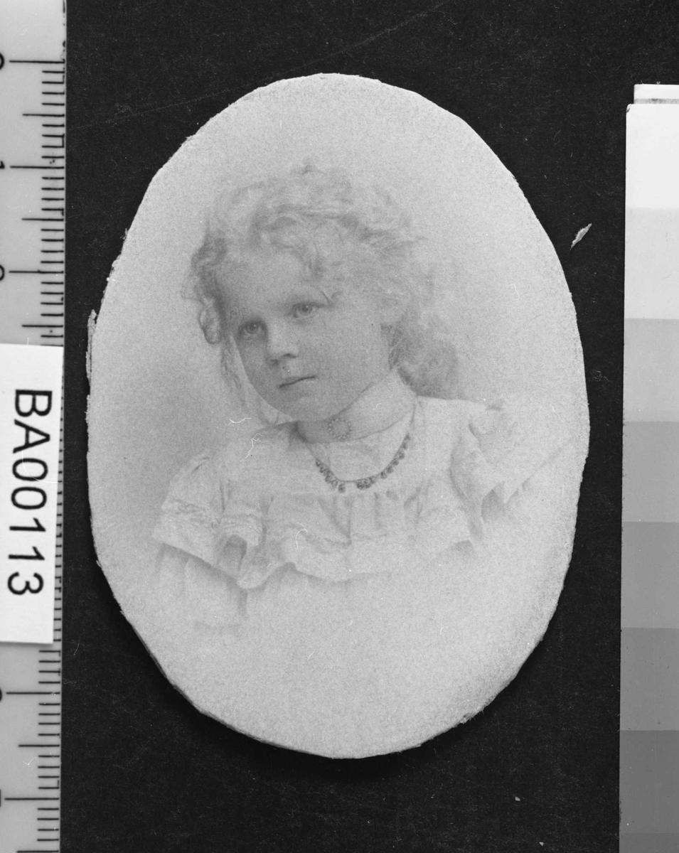 Barneportrett, pike i hvit kjole med halskjede og langt lyst krøllete hår samlet i hestehale.