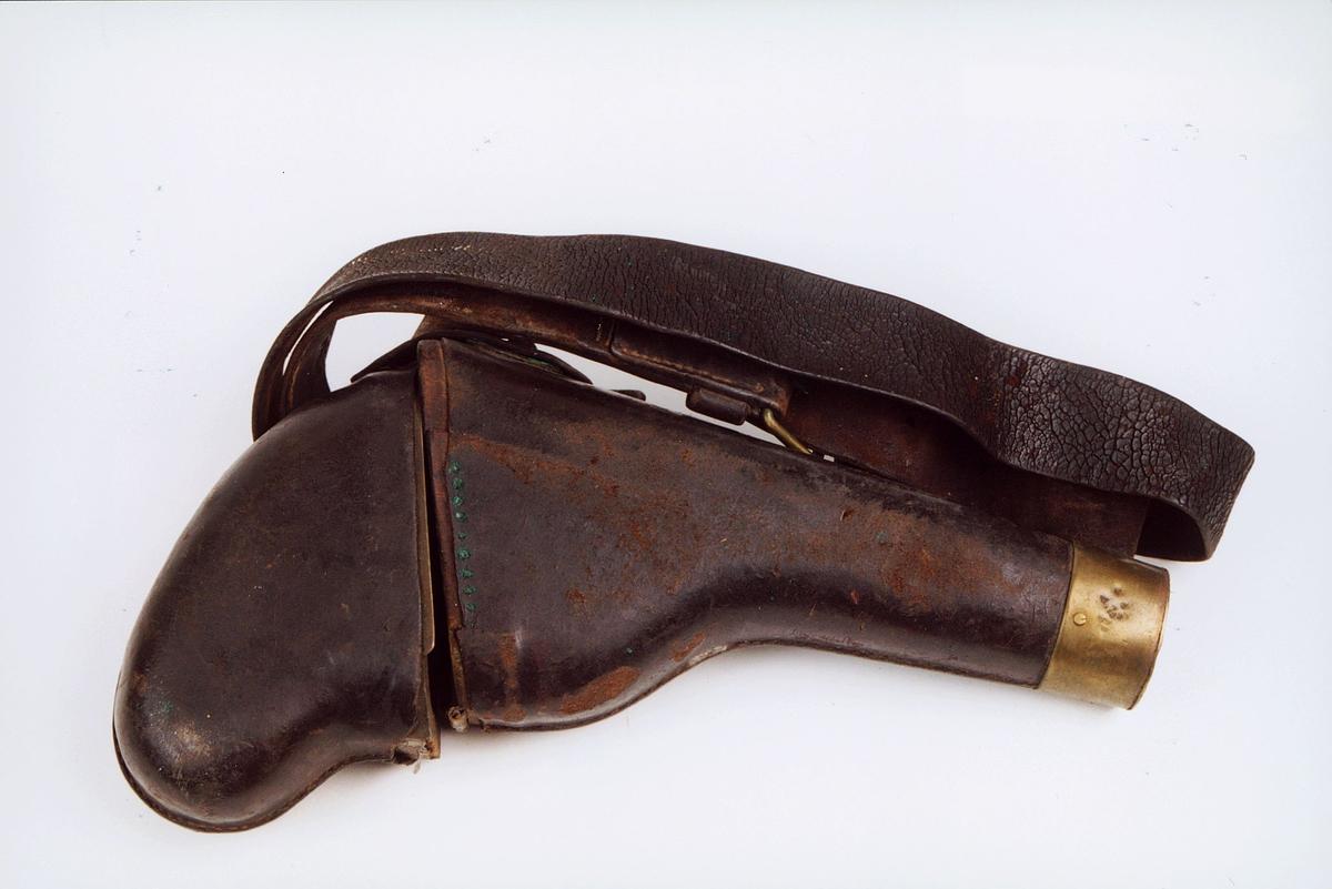 Lærhylster til revolver nr. P0712. Lærovertrukket trefutteral med topp festet med gangjern av messing. Dupsko av messing og bred sort lærrem med messingspenne. (sjelden)
