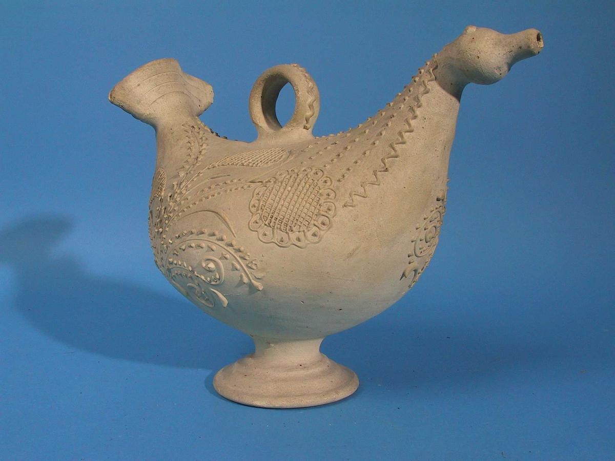 Gjenstanden er formet som en fugl. Dekorert med ranker, blomst oppdelt i små ruter og med tunget bord.