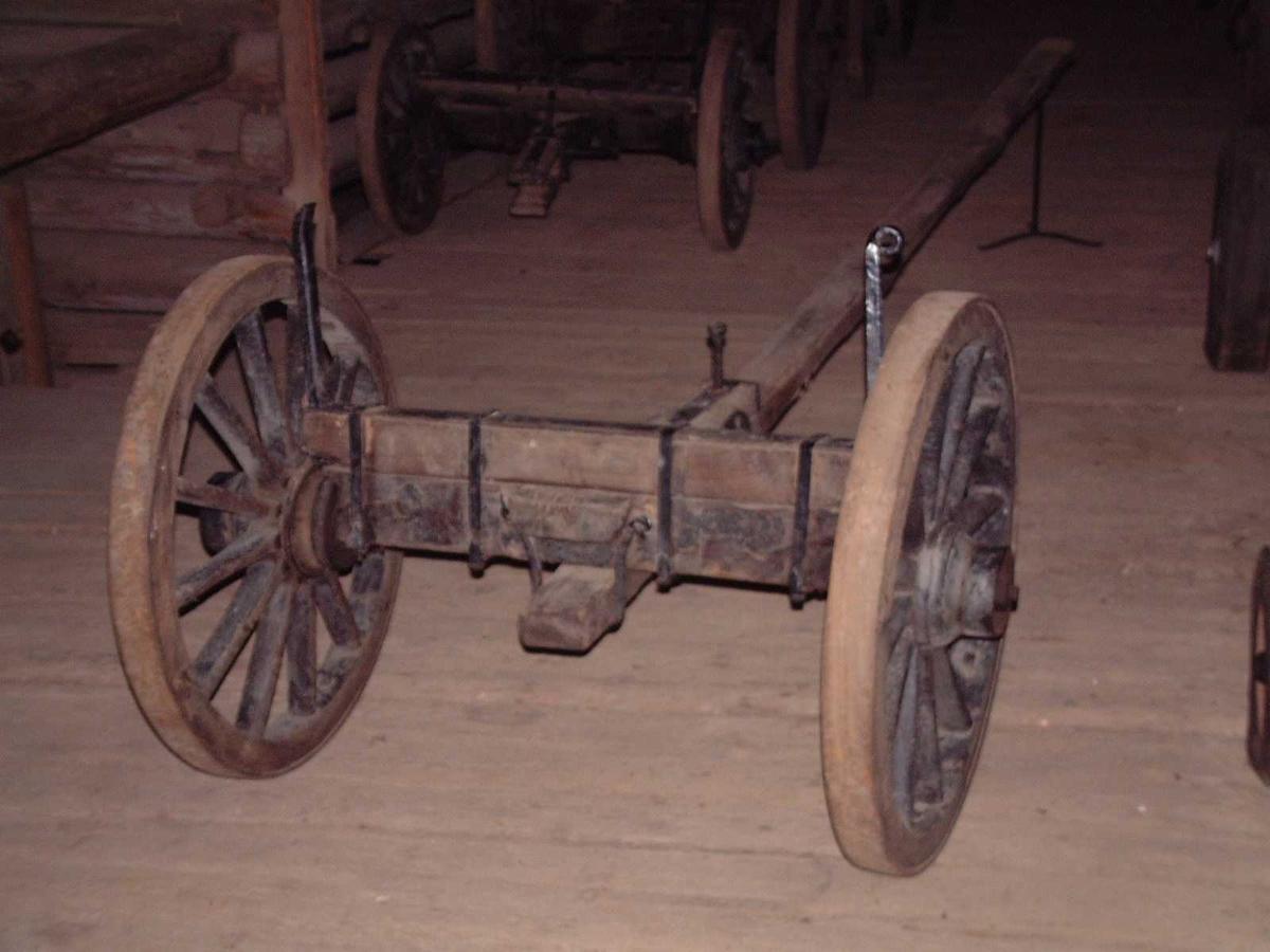 Kraftig treaksel med rektangulært tverrsnitt. Bom med løse jernkeiper. Mellomstang med bolt. Jernstengte trehjul med svak styrt. 6 fell, 12 eiker.