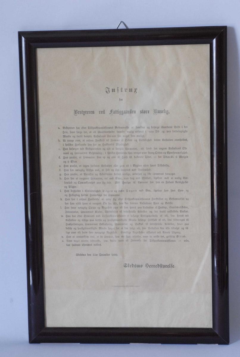 Rammen i form av flat halvstaff, lakkert. Instruksen er skrevet med gotisk skrift, med tittel i 3 linjer, tekst i 14 punkter, dato og signatur.