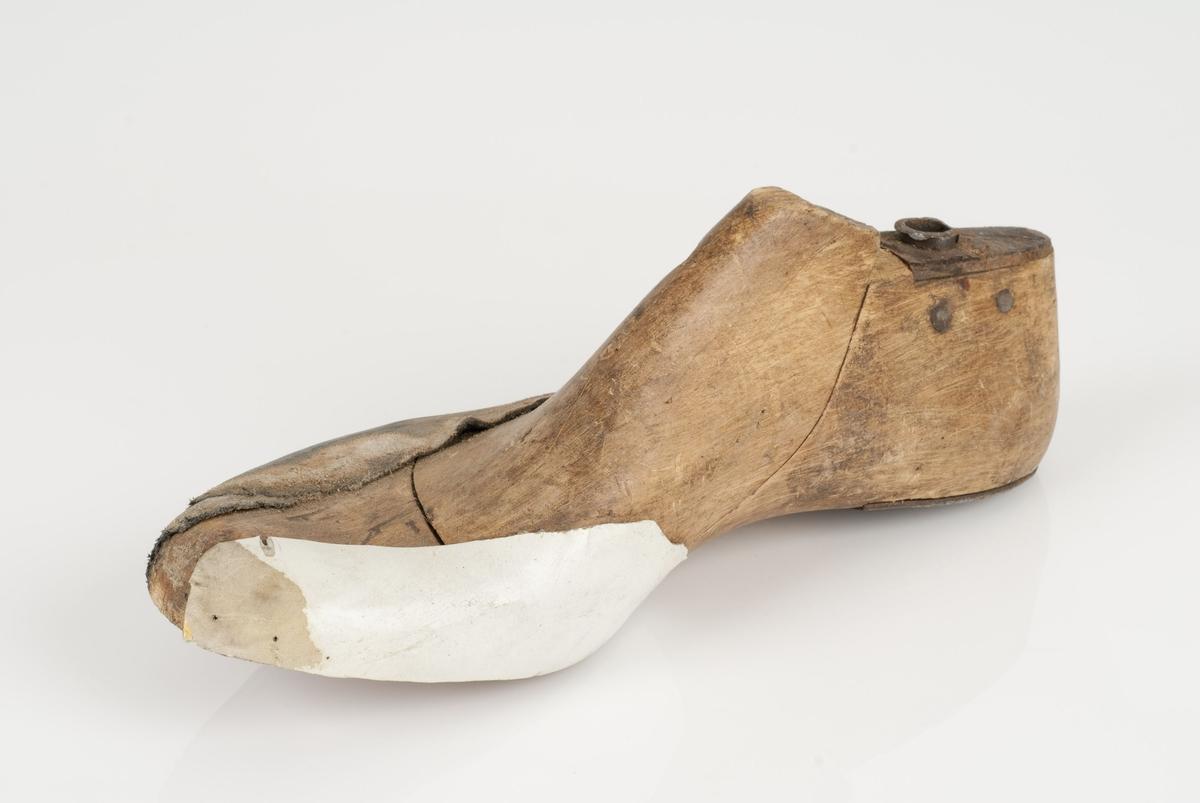 En tremodell i to deler; lest og opplest/overlest (kile). Høyrefot i skostørrelse 41, og 6 cm i vidde. Hælstykke av metall. Påfestet skinnfiller. Lestekam av skinn.
