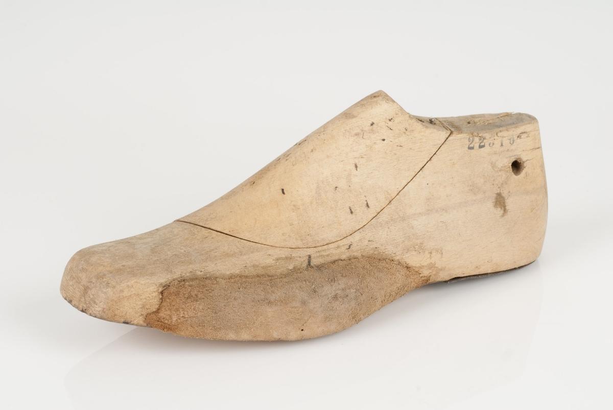 En tremodell i to deler; lest og opplest/overlest (kile). Venstrefot i skostørrelse 42, med 9 cm i vidde. Hælstykket av metall.