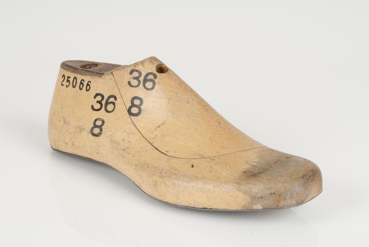 En tremodell i to deler; lest og opplest/overlest (kile). Høyrefot i skostørrelse 36, og 8 cm i vidde. Lestekam i skinn. Såle i metall.