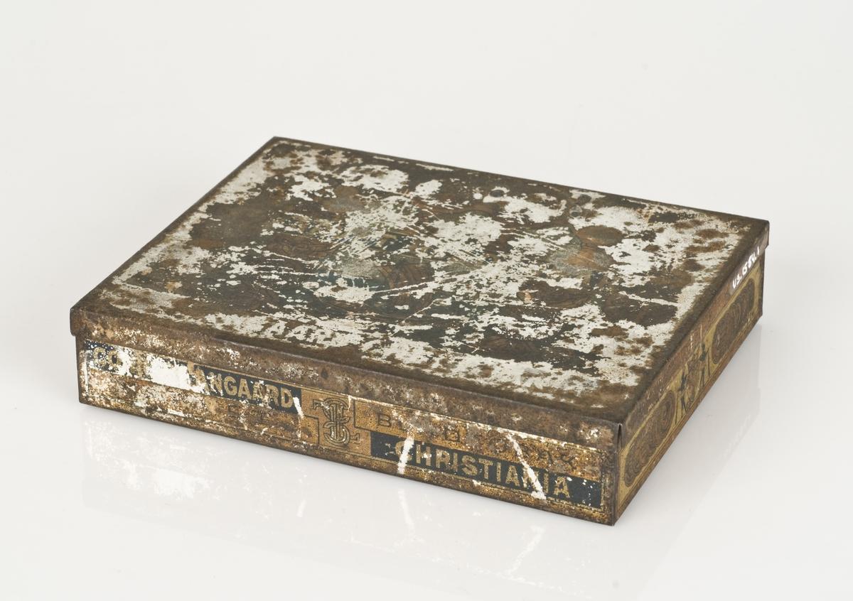 Maljer (til bekksøm støvler) av metall i en metalleske. Påført tekst på esken.